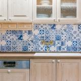 Tradice každým coulem: Celodřevěná kuchyň, stylová baterie a stěna obložená dlažbou s tradičními jihoevropskými modrými vzory. Dokonalá kombinace!