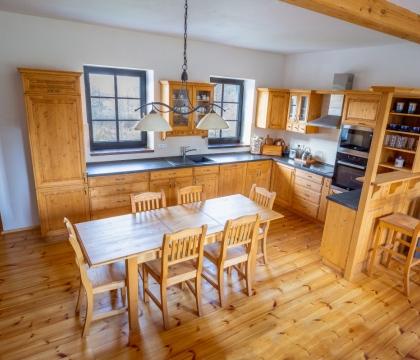 Nezbytný sedací nábytek je ze stejného materiálu jako je kuchyňská linka a stejně tak i podlaha z masivu - skvělá ukázka komplexního uvažování majitelů.