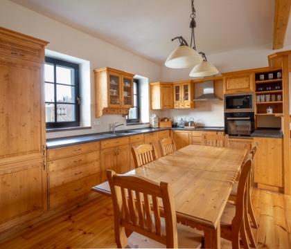 Velký prostor obývací kuchyně si žádá i velkorysé architektonické řešení kuchyňské linky: masivní, ale přitom lehké a přehledné, vyrobené ze smrkového masivu.