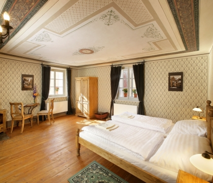 Pokoj penzionu vybavený rustikálním nábytkem